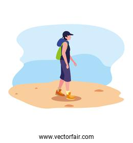 young man with backpack walking sand