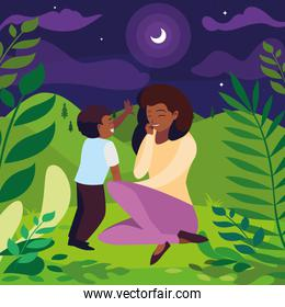 pretty beautiful black mother with son in the field at night