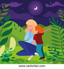 beautiful mother with son in the landscape at night