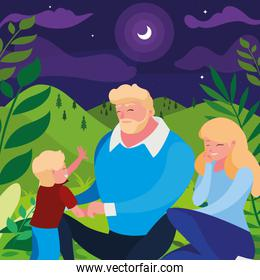 parents couple with son in the field at night