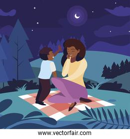 beautiful black mother with son in the field picnic day