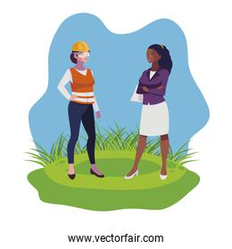 female builder and afro engineer woman on the lawn
