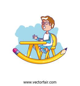 little student boy sitting in school desk with pencil