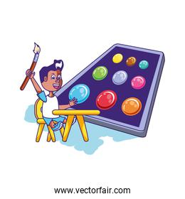 little student boy sitting in school desk and palette colors