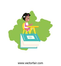 little student girl sitting in school desk with book