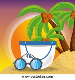 summer bag and sun glasses over sand with a beautiful sunny beach