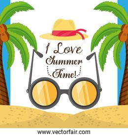 summer hat and sun glasses over sand with a beautiful sunny beach