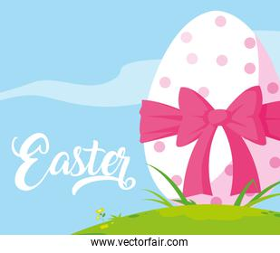 decorated easter egg with bow in grass