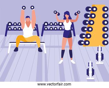 athletic couple lifting dumbbells in gym