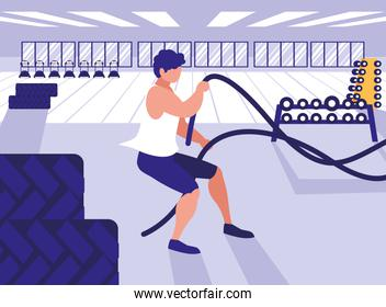 young athletic man with rope sport in gym