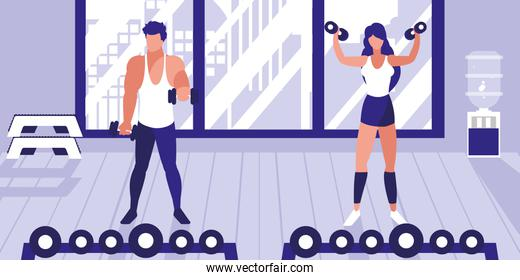 young athletic couple lifting dumbbells in gym