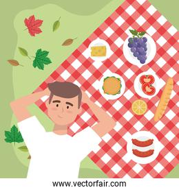 man with grapes and snack food in the tablecloth