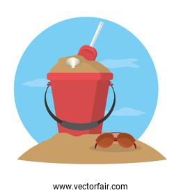 sand bucket with shovel toy and sunglasses