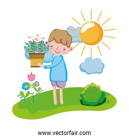 little boy lifting houseplant in the landscape