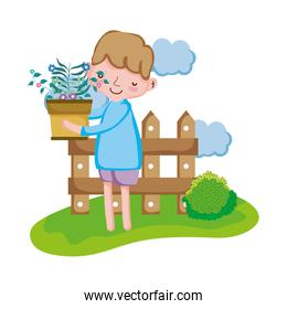 boy lifting houseplant with fence in the landscape