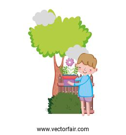 little boy lifting houseplant with tree and fence