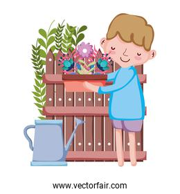 boy lifting houseplant with sprinkler and fence
