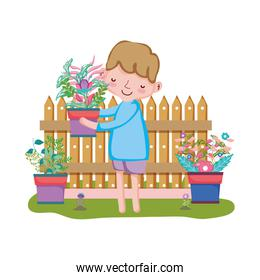 boy lifting houseplant with fence in the garden