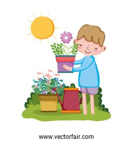 boy lifting houseplant with sprinkler in the garden