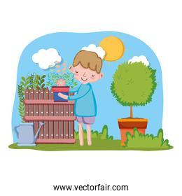 little boy lifting houseplant with fence and tree