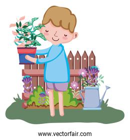 boy lifting houseplant with fence and sprinkler