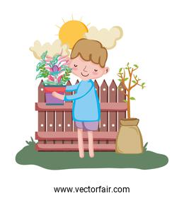 little boy lifting houseplant with fence in the garden