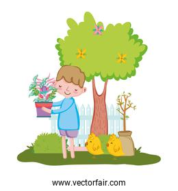 little boy lifting houseplant with fence and chick