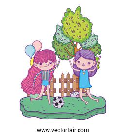 cute little girls playing soccer in the landscape