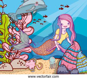 woman mermaid with dolphin and stingray in the sea