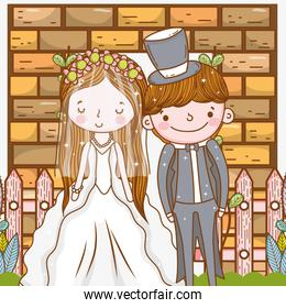 woman and man wedding with fence and brick wall
