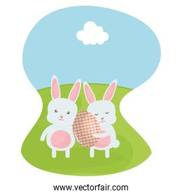 cute rabbits with easter egg painted in the field