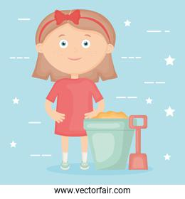 little girl playing with sand bucket and shovel