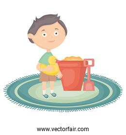 cute little boy with sand bucket and ducky