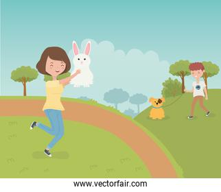 woman with rabbit and boy with dog outdoor pet care