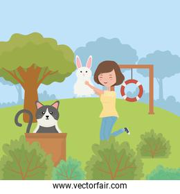 woman with rabbit and cat with box in the park pet care