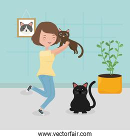 woman holding brown cat and black cat sitting in the room pet care