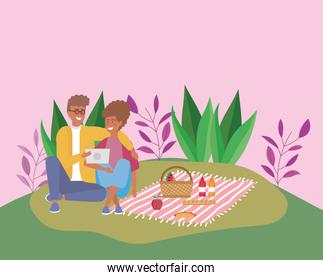 couple with tablet with food blanket picnic outdoor