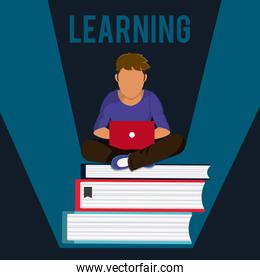 Student with laptop seated on books