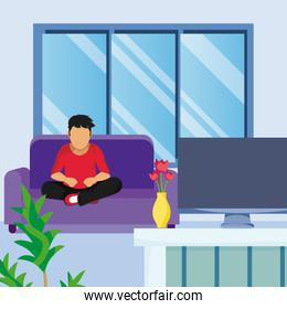 Young man seated on armchair seeing tv