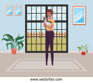 young afro woman lifting cute dog indoor the house