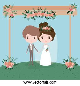 sky landscape scene background in grass with couple of just married under decorative frame in wooden poles with floral ornaments