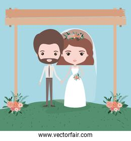sky landscape scene background with couple of just married under decorative frame in wooden poles and floral ornaments in grass
