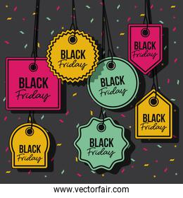 black friday with set of discount offer tags in yellow magenta and green and pendant of threads in black background with confetti colorful