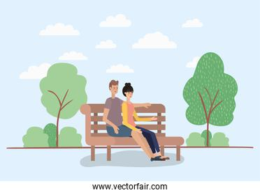 young couple lovers sitting on park chair