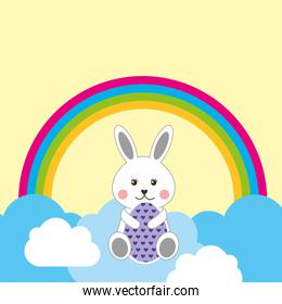 cute rabbit sitting in clouds decorative egg and rainbow