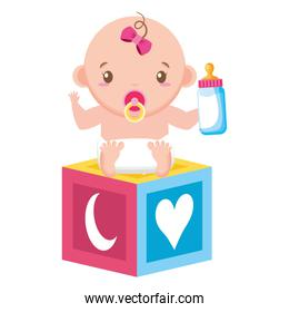 cute little baby girl with block toy and milk bottle