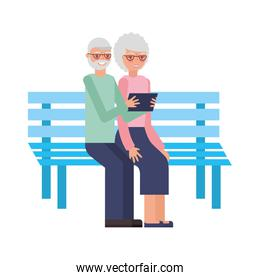 cute grandparents in park chair with device tablet