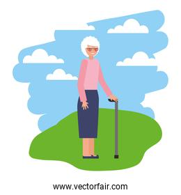 cute grandmother with walking stick in grass