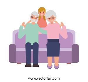 grandparents with granddaughter sitting on sofa