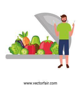 bearded man with fresh vegetables and fork knife